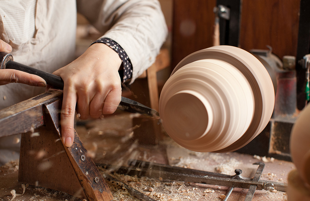 First Maiko takes off the wood around the body of the bowl, removing any excess wood that isn't needed.