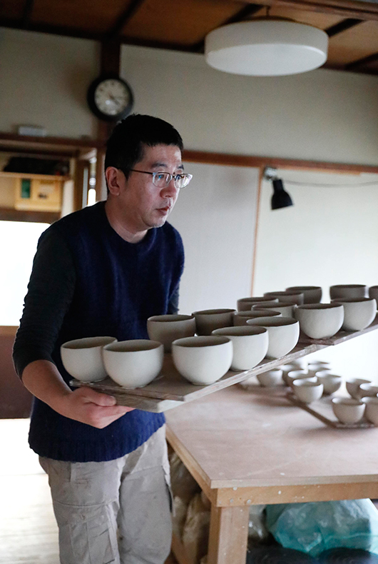 Makoto Asebi carries the coffee cups to his pottery kiln at the side of his garden.