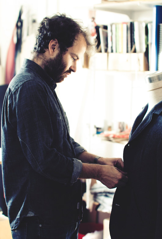 Marcus Uran in his studio, measuring up an outerwear piece from the Metsa collection.