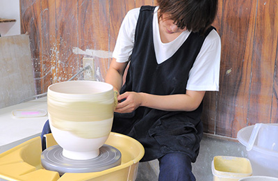 Misa applying some of her glaze to a big porcelain pot that she's made in her workshop.