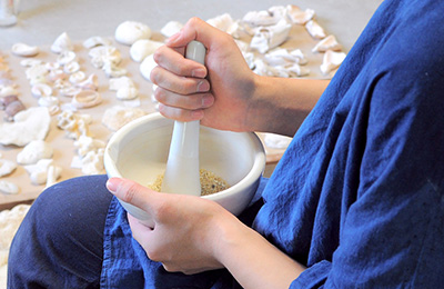 Using a pestle and mortar to ground down the substances in to a paste, she can then use this to mix with other powders and create interesting glaze effects with a natural tone.