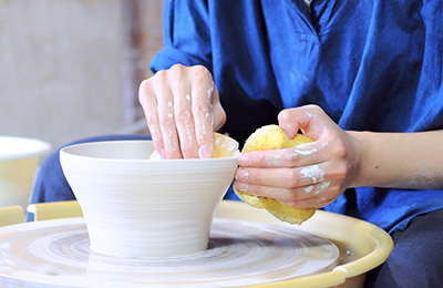 She begins to pull up the clay wall in to the desired shape, making sure the clay is even and the form is aesthetically pleasing.