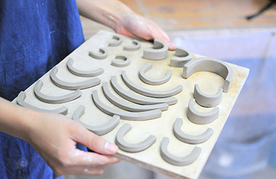 Each handle is shaped by hand, they are then attached to the vessels before they fully dry out.