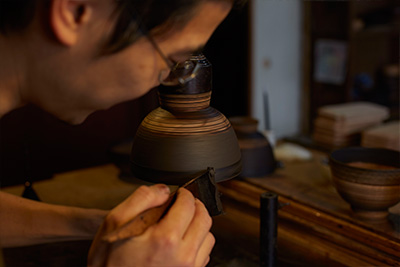 Akihiko Sugita applying lacquer to a vessel in his workshop.