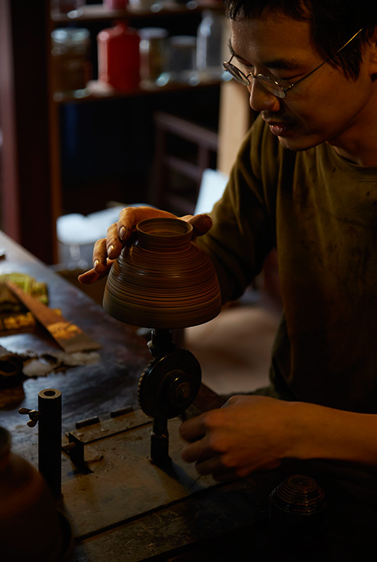 Akihiko Sugita places the bowl on a mechanical wheel that spins the bowl, meaning that he can apply the lacquer without touching the bowl.