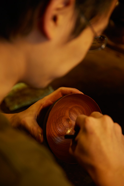 Akihiko Sugita stays applying the lacquer to the inside of a small bowl.