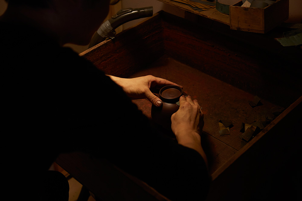 The bowl is sanded from the foot downwards, they repeat this each time to make sure the surface is perfectly smooth.