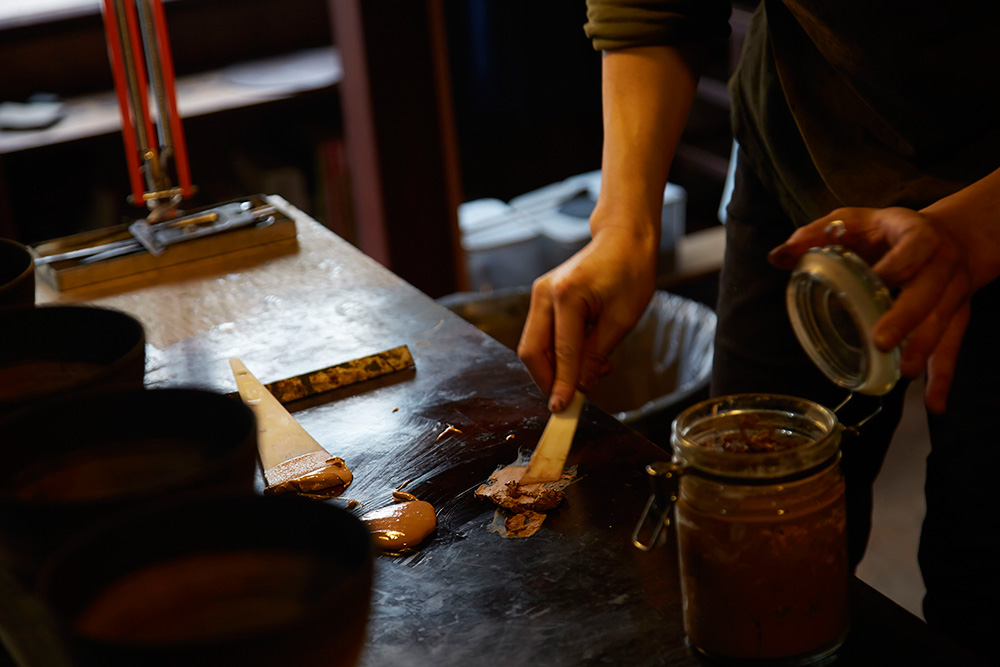 Akihiko places some urushi and pigment on the table, this will then be mixed to create the desired thickness and colour.