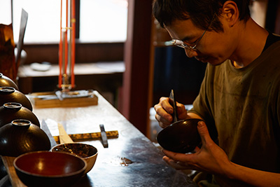 Later he applies lacquer to the inside of some smaller bowls, a different colour to the exterior.