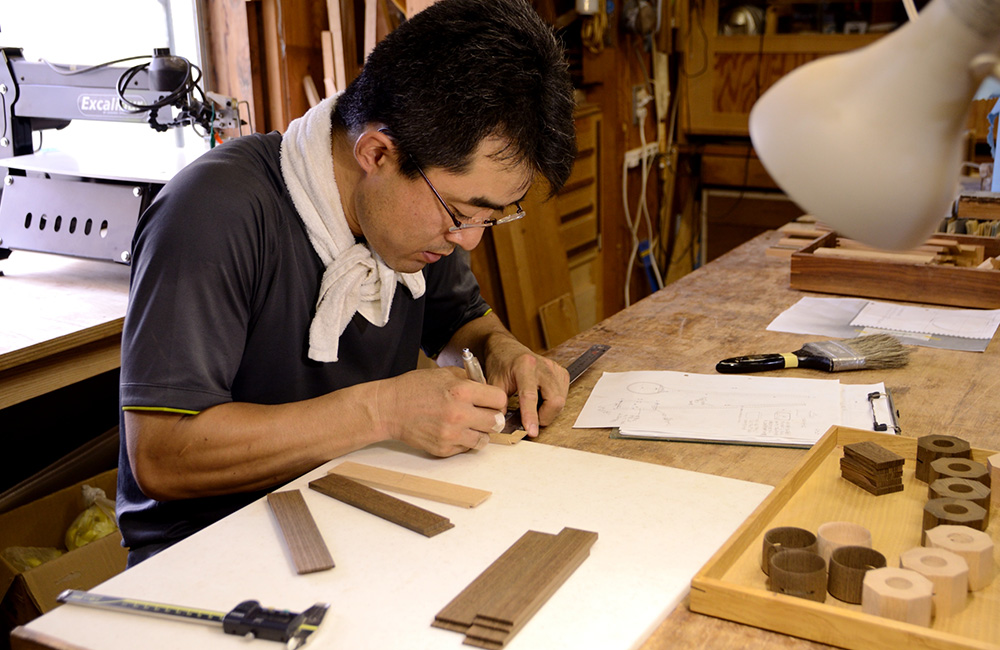 He measures exactly the right size for the handle, referencing drawings that he's made in the past.