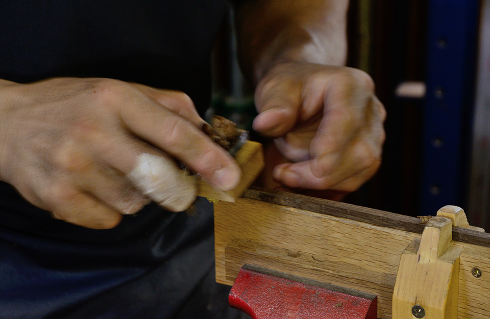 Perfecting the shape of the handle by hand, making sure the character of the wood will be showing in the final object.
