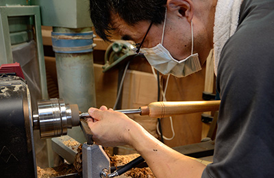 Yusuke Tazawa on the lathe turning the walnut coffee scoop to the desired shape.