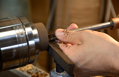 He uses a number of different chisels to perfect the form.